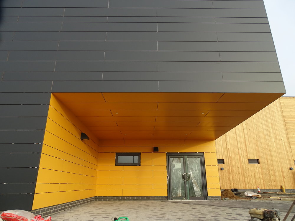 Rockpanel Rockclad rainscreen panels on an aluminium framing system to walls and soffit of sports hall