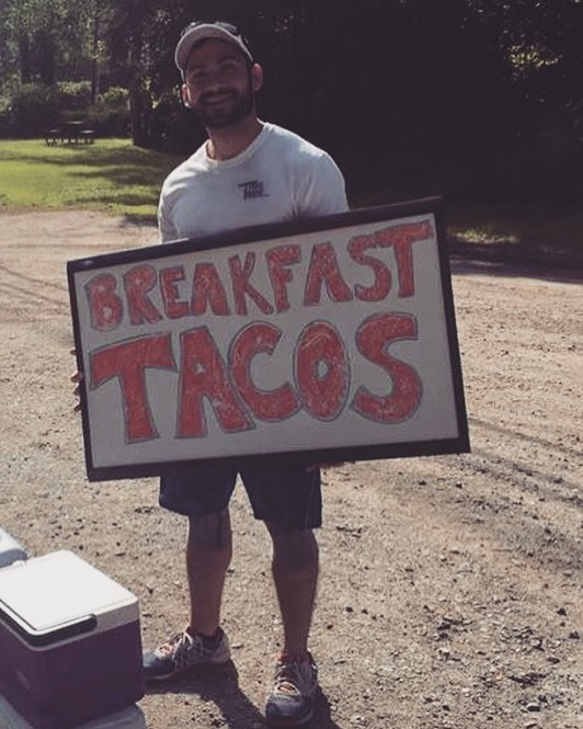 Tito on the side of the road with coolers full of homemade breakfast tacos.