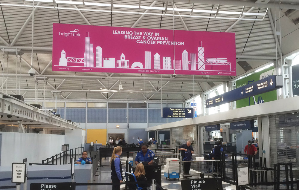 A printed poster that is hanging in the O'Hare International Airport, Terminal 1 security line. The poster is 24 x 6 feet and incorporates Chicago with the Bright Pink brand.