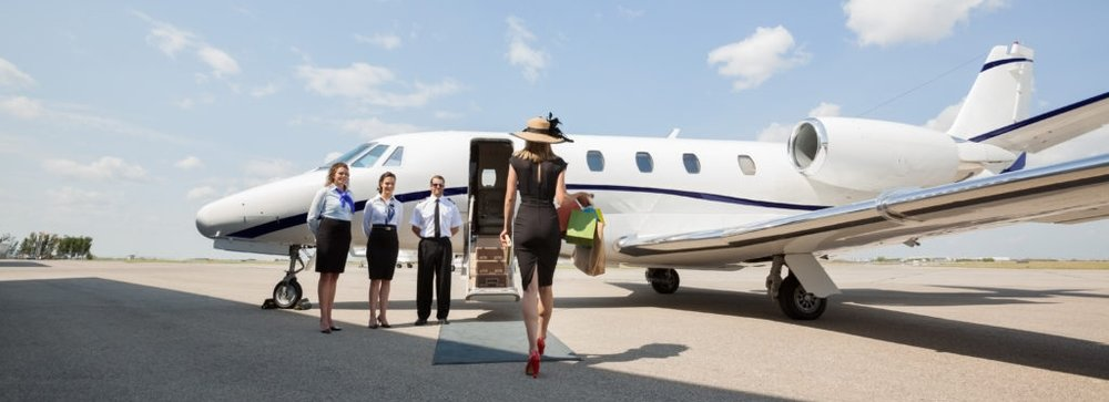 Rich Woman Walking Towards Private Jet At Airport Terminal