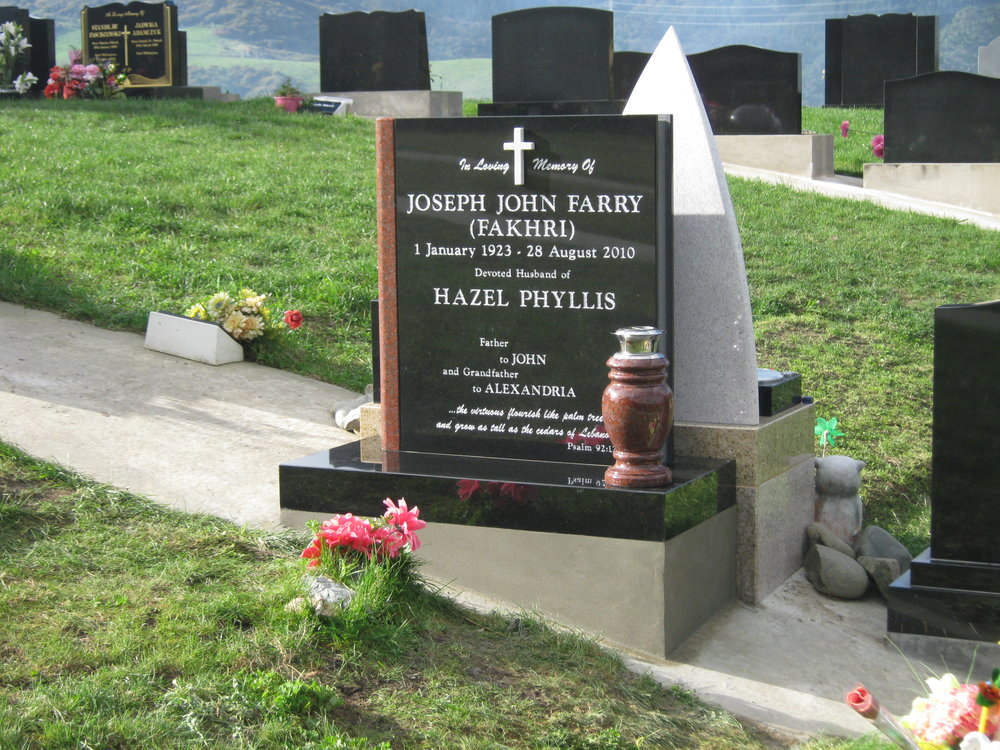 Black granite headstone. Closed book design, Pohutukawa red turned vase