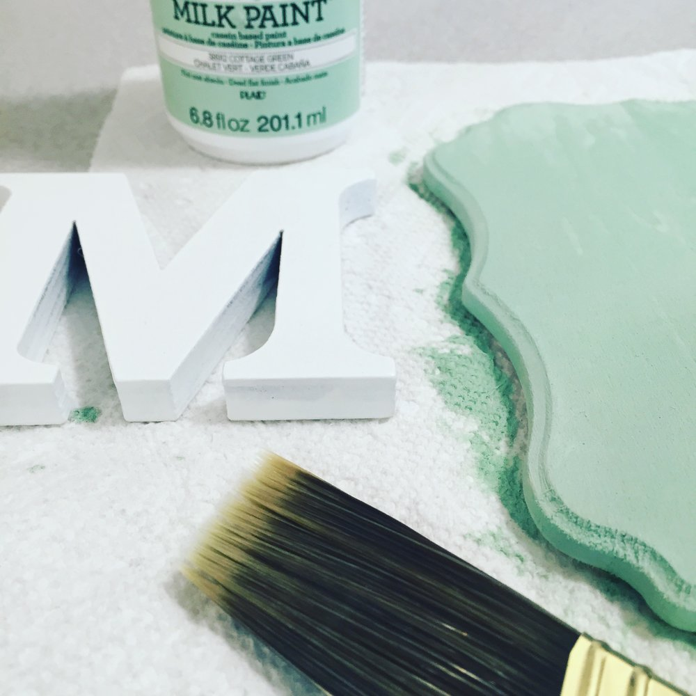 """Painting the wood with teal milk wash, before glueing the """"M"""""""