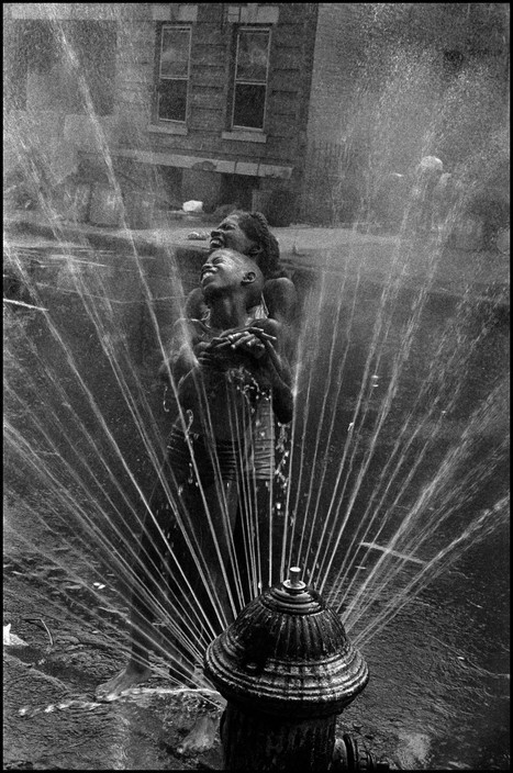 The fire hydrants are opened during the summer heat. Harlem, NYC, USA. 1963