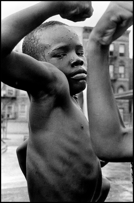 "A young boy plays ""tough"" in the streets of Harlem. New York, USA. 1963."