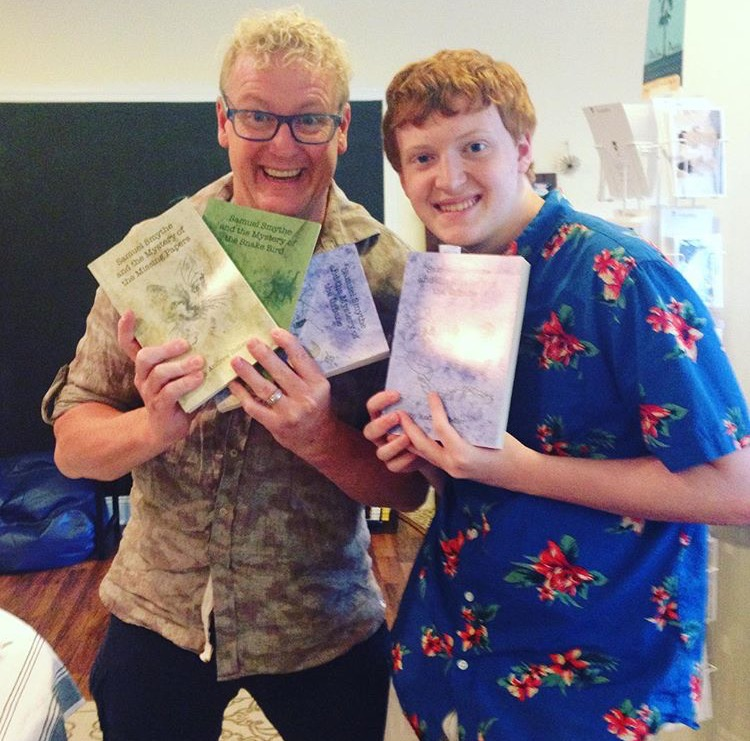 Andrew Heller, left, holds up copies of his novel trilogy with his son and inspiration for the series, Sam, right.