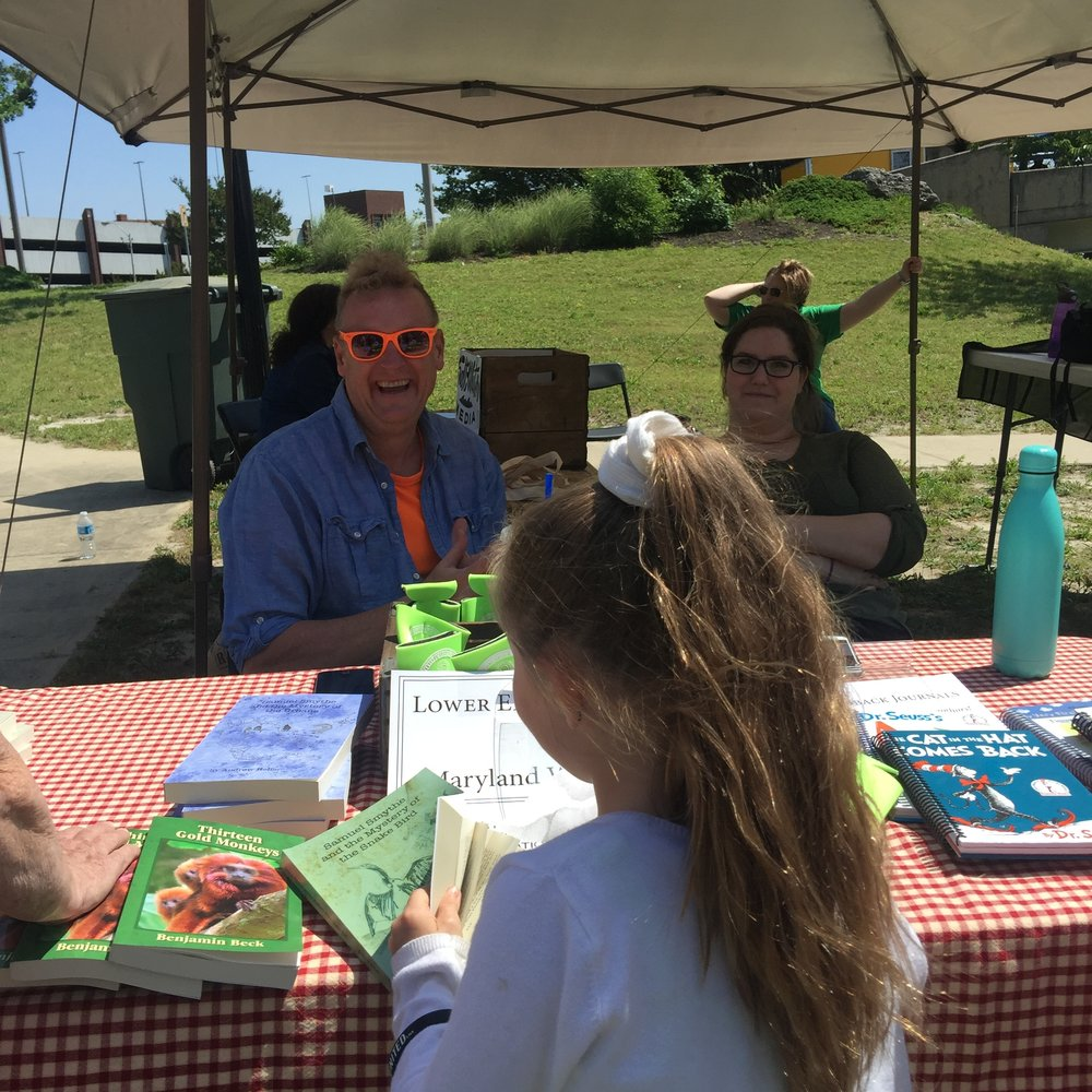 Young adult fiction author Andrew Heller entertains a reader while Robin Beauchamp hangs out under the Lower Eastern Shore - Maryland Writers' Association tent.