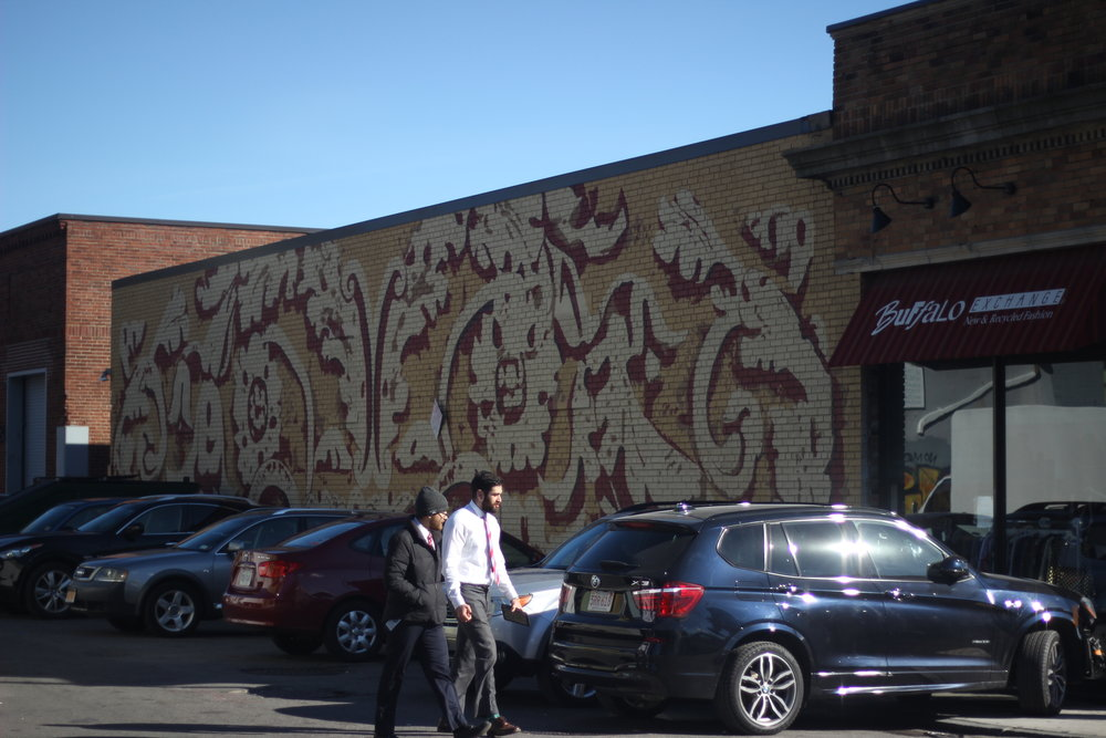 Two gentleman walk from their car past a mural. Businesses covered in art seems to have become a trend over the years attracting college age students to live there. (Artist Unknown.)