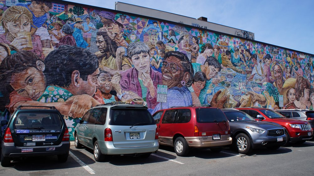 David Fichter's mural  The Potluck,  featuring faces you could see walking around Cambridge. Fichter sought help from local teenagers cementing the neighborhood feel in such a homey work of art.