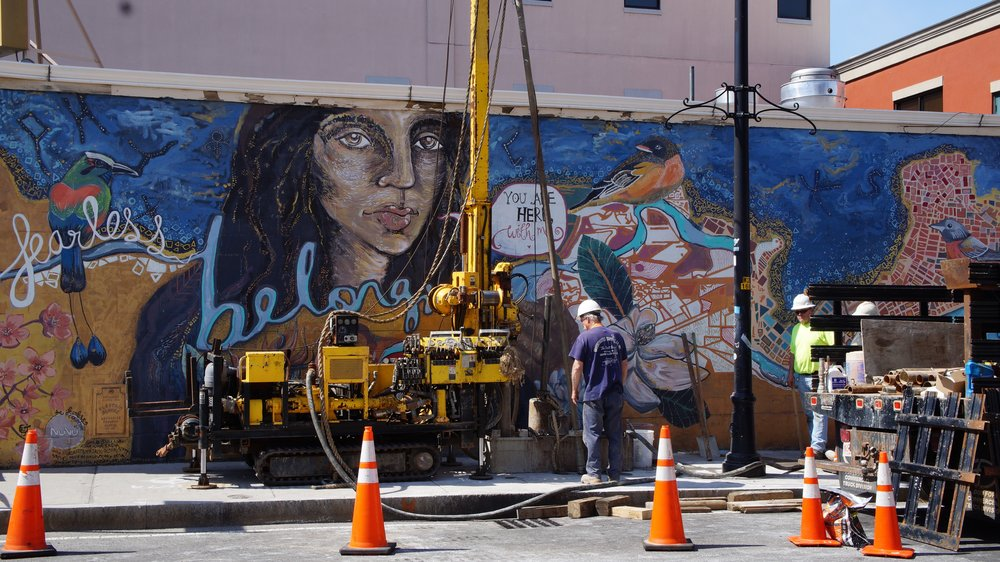 Construction workers maintain a sewer in front of Suleman's inclusive mural on a hot April day.