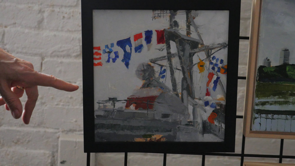 Carol's hand points to a painting of Charlestown's Navy Yard, a project commissioned for a special, commemorative event at the location.