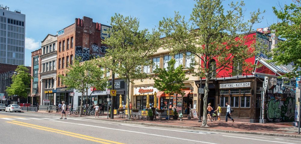 Trees, graffiti, and a variety of storefronts give color to Massachusetts Ave in Central Square.   Photo courtesy of equityapartments.com.