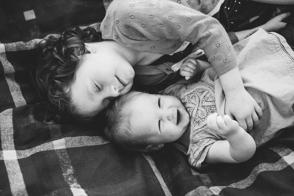 Sisters snuggling on blanket Portland Oregon Lightheart Studios Family photography