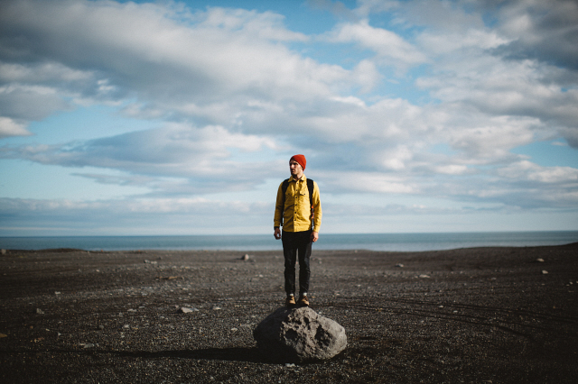 Mid adult man standing on top of boulder on volcanic landscape looking away Iceland