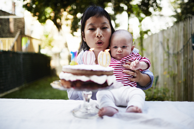 Mother holding baby son blowing out candles on cake