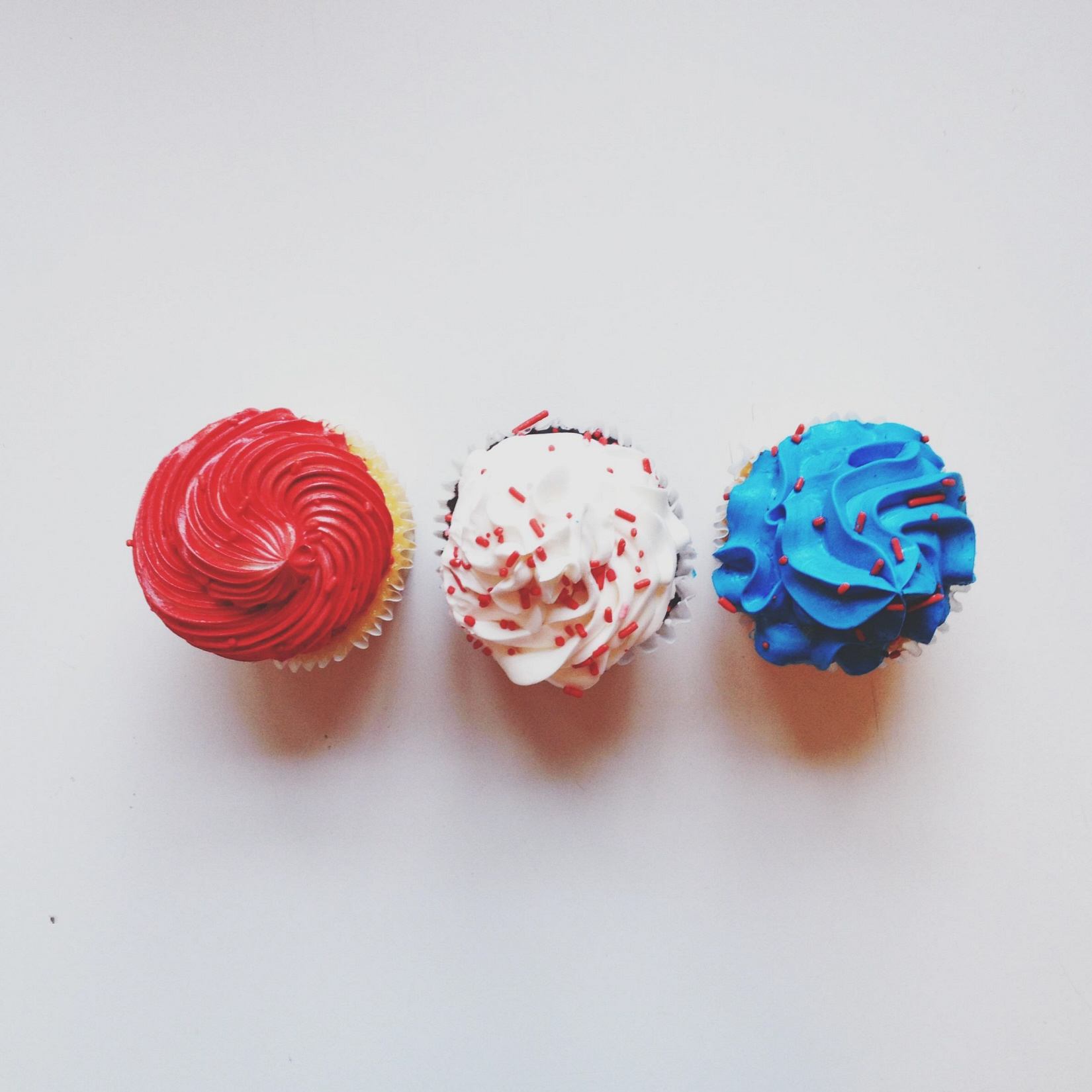 Three cupcakes decorated with red white and blue whipped cream