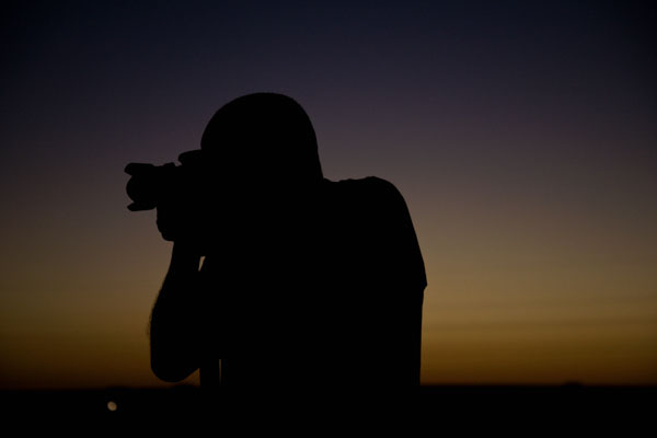 Silhouette of a photographer in front of a sunset