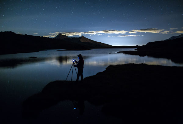 Photographer admires reflection on Rossett Lake at night, Gran Paradiso National Park, Alpi Graie (Graian Alps), Italy, Europe