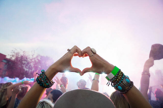 Woman forming heart-shape with hands in crowd at summer music festival