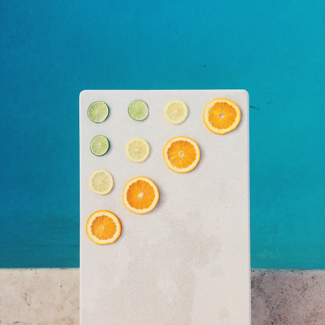Slices of orange and lime on edge of swimming pool