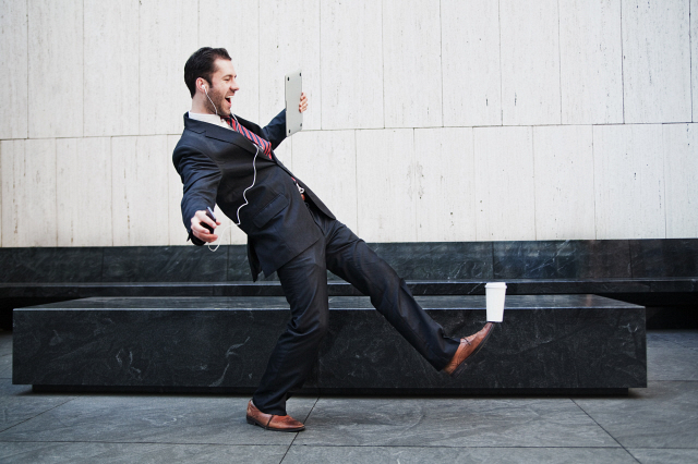 Businessman holding laptop and balancing coffee on his foot