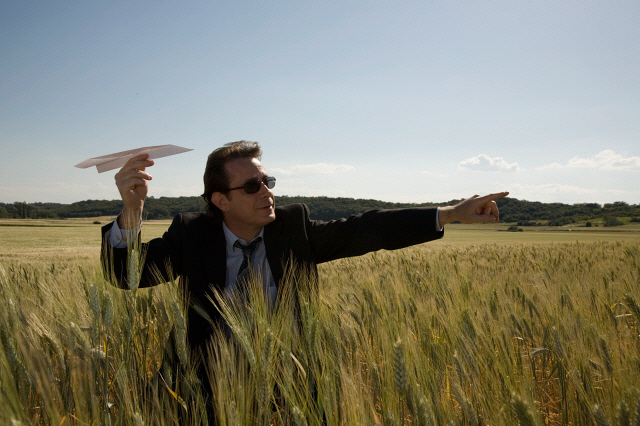 Businessman aiming paper plane in wheat field