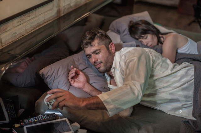 Man sleepless in bed looking at alarm clock with wife lying beside him