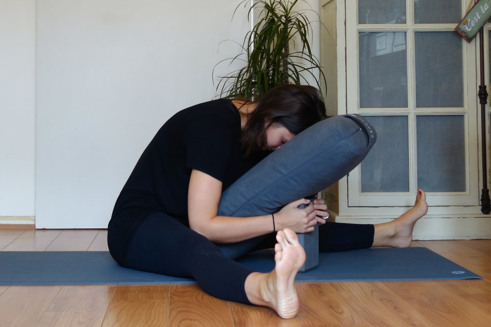 seated forward fold with bolster you go do yoga