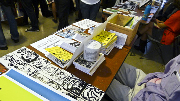 "The blue variant of the ""Hi, I'm Daniel"" poster can be seen in the lower right. This photo is from the 1st LA Zine Fest in 2012, which took place upstairs at the Last Bookstore in Los Angeles, CA."