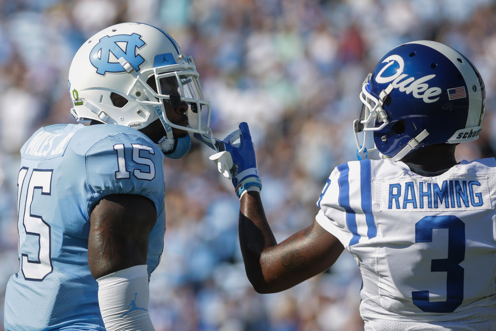 North Carolina safety Donnie Miles (15) and Duke wide receiver T.J. Rahming (3) exchange words during a game in Kenan Memorial Stadium on Sept. 23, 2017.