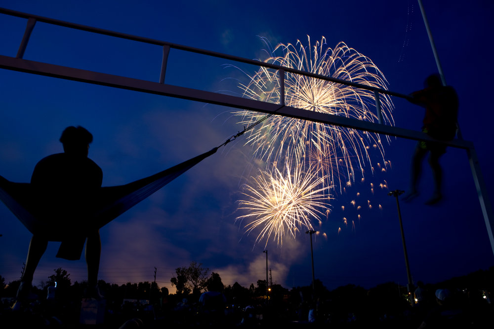 Nahuel Recanarren, 19, swings in his hammock while Jackson Reed, 14, climbs up to get a better view of the fireworks at the River's Edge Sports Complex in Roanoke, Va. on July 4, 2018.