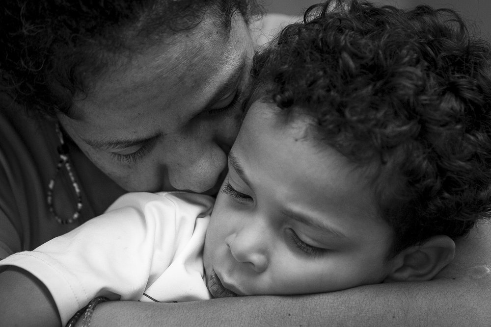 Minerva hugs Mateo at the dining table during dinner on Sept. 30, 2017 in the Congregational United Church of Christ in Greensboro, NC. Minerva, a widow, raises her two youngest sons as a single mother in the church. Her eldest son, Eduardo, is blind and lives alone in Minerva's home in Winston-Salem, NC.