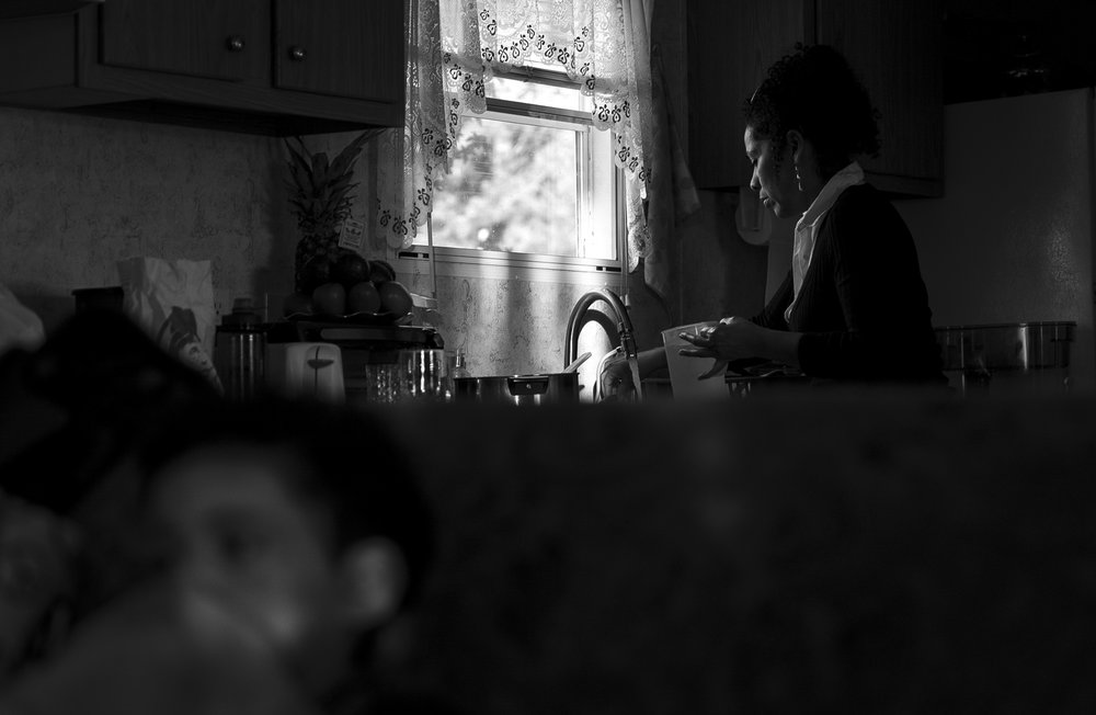Minerva washes the dishes in her Winston-Salem home while Mateo (bottom left) watches TV on Nov. 16, 2017. As a single mother living with her three sons, she has a hard time keeping up with the chores around the house.