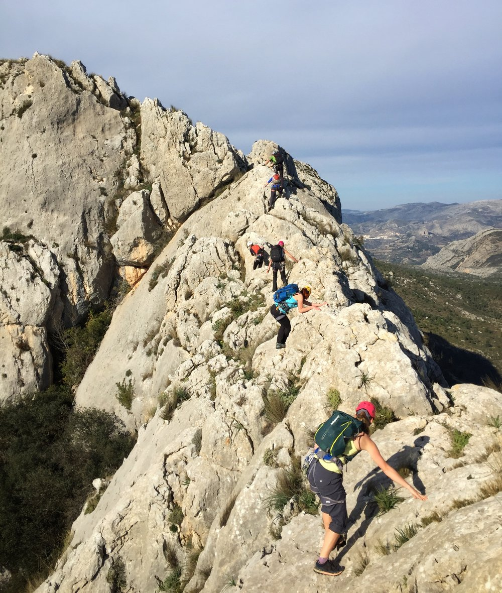 A group traversing the Bernia Ridge, Costa Blanca, which includes scrambling, abseiling, and rock climbing