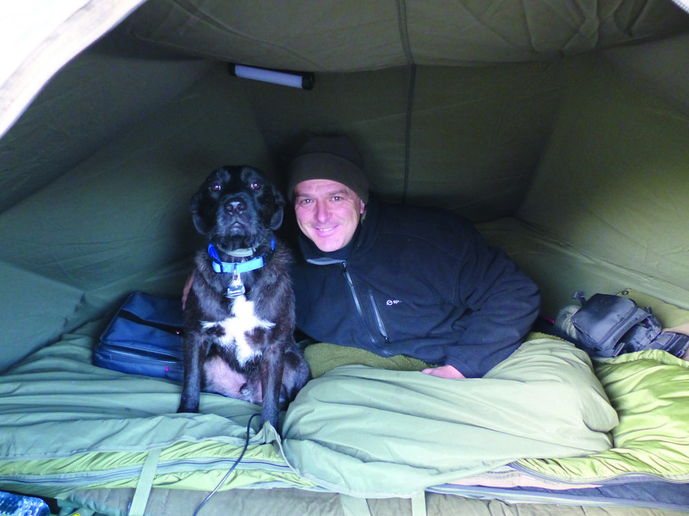 Stan the carp dog keeping me warm in the depths of winter. Using a brolly instead of a bivvy allows you to see and hear so much more. I never zip up in a bivvy