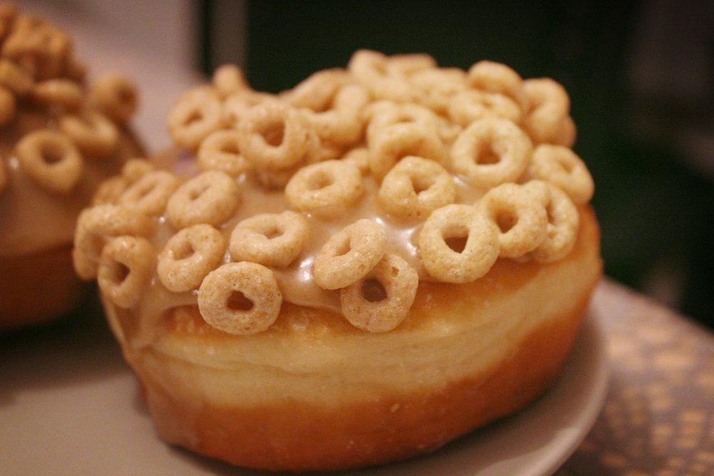 Nostalgískur kleinuhringur fylltur sætri súrmjólk og hjúpaður með karamellu og hunangs-cheerios