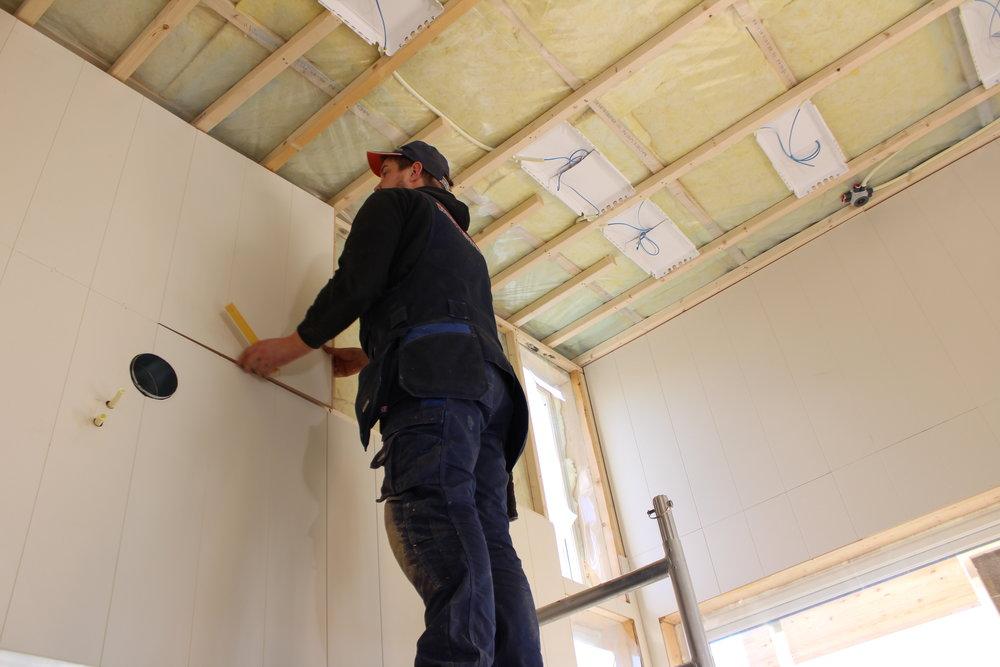 Jørn Ole Viddal innreiar ei av leilegheitene i øvste etasje og monterer her veggplater.