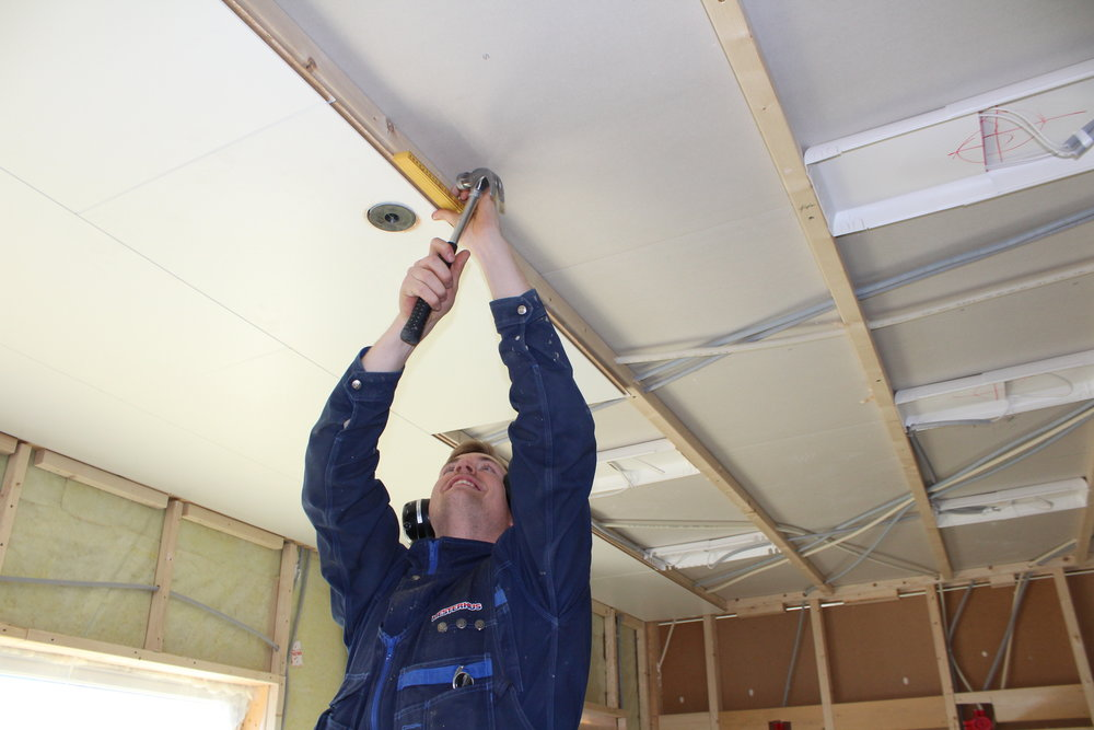 Robin Urke held no på med å montere takplater i underetasjen.