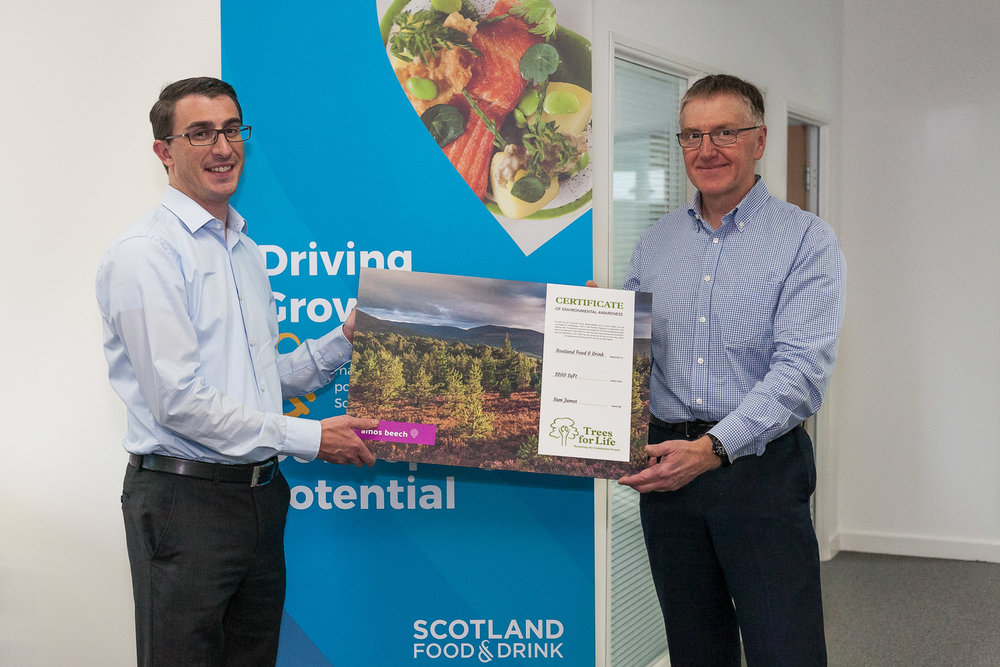 Operations director Roy James hands over the Trees for Life certificate to Dennis Overton, chairman of Scotland Food and Drink