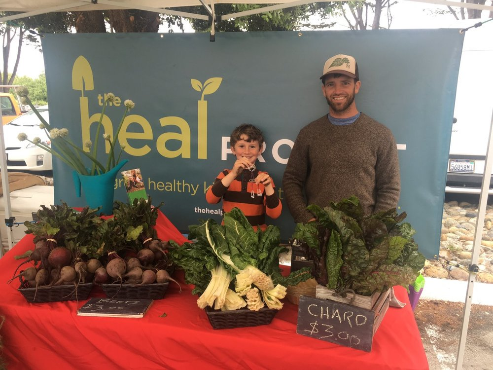 Fisher with Farmer Jon at our market booth participating in our Jr. Marketeer Program