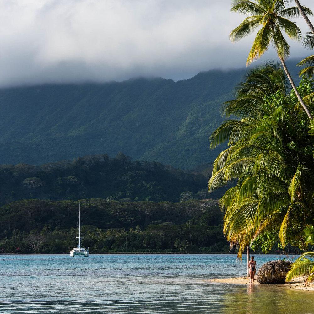 Our Te Mana Travels catamaran anchored near a lagoon in Bora Bora, one of the Society Islands in French Polynesia.