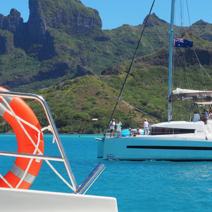 Te Mana Travels' Tahiti Escapade 2019 catamaran anchored near a lagoon in French Polynesia.