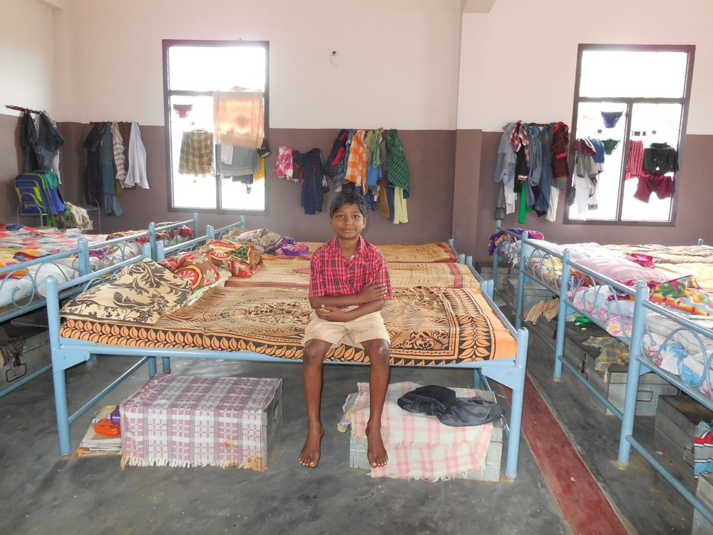 A Young Boy sitting on his new bed inside the newly completed home.