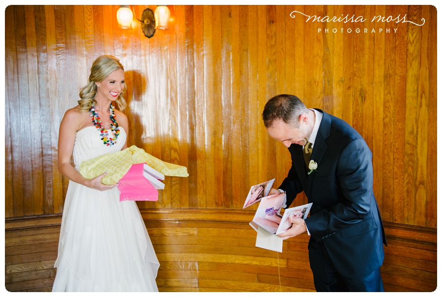 Groom opening his boudoir book gift from his wife on their wedding day, what a great surprise! Image by Marissa Moss Photography