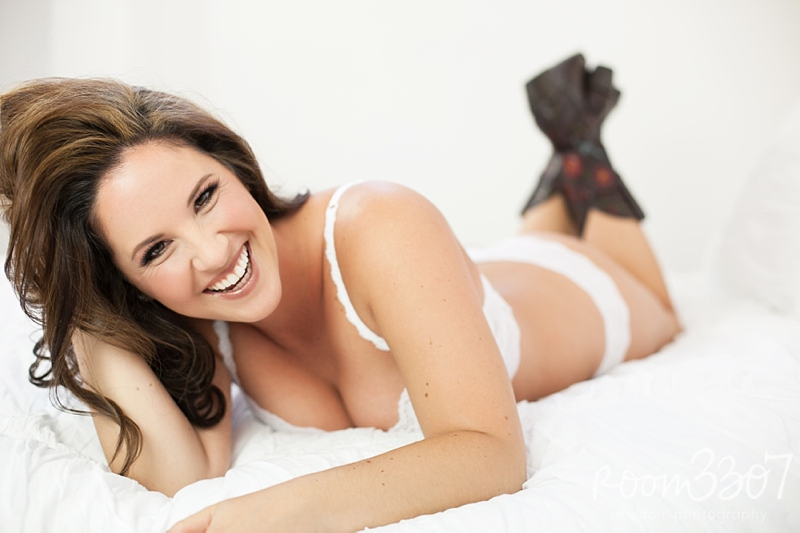 Sexy laughing boudoir photos, white lingerie with cowboy boots on bed, by Room 3037 boudoir photography in Tampa, Florida. Hair and makeup by Jess Waldrop makeup artists.