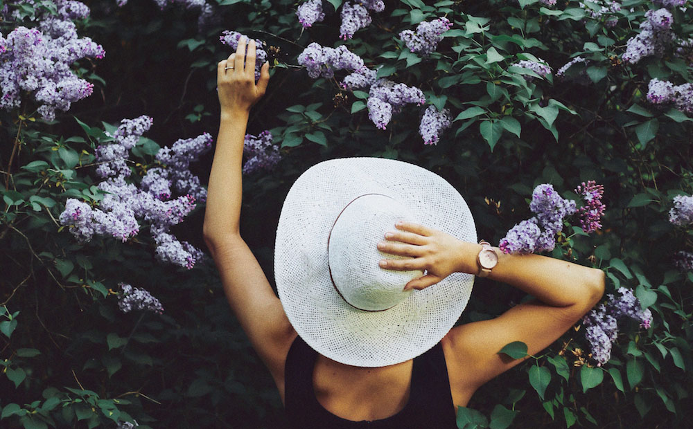 woman in hat tending purple lilac bush