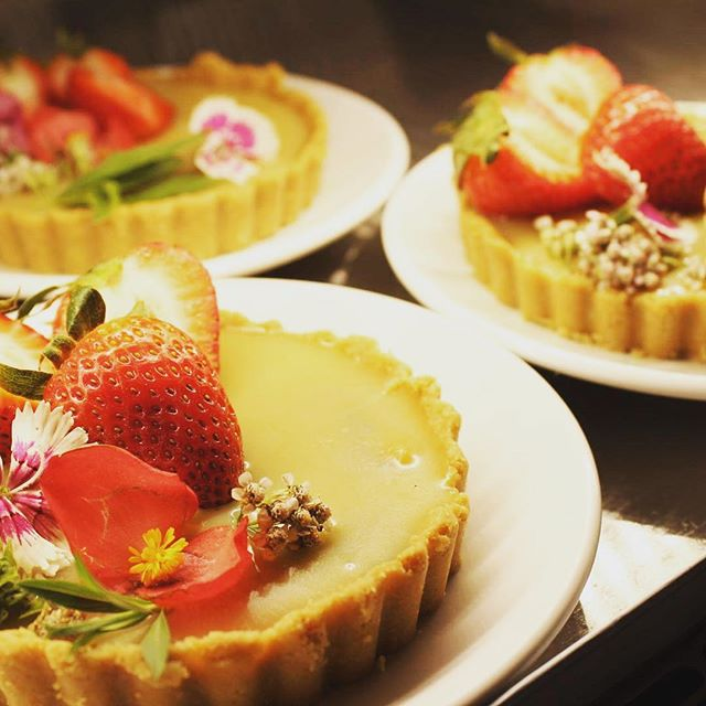 Stop in tomorrow for a decadent chocolate ganache caramel tart garnished with strawberries and flowers and herbs grown by @magnoliamooncollective 🌸 #macandmoon #edibleflowers #flowertart #glutenfreevegan #vegannola