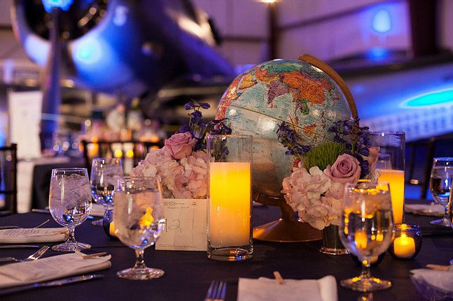 Table numbers were made from vintage postcards, centerpieces were a combination of vintage globes and stacked vintage travel books. Flowers were arranged in family mint Julep cups. Photo:  Chris Isham Photography