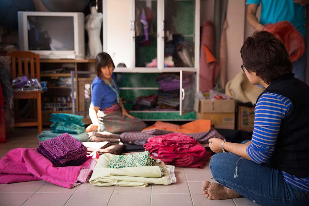 Gina Hope (right), founder of global groove life, Choosing fabrics with Dia (Left), the master tailor and co-op coordinater in Chom Thong Village.