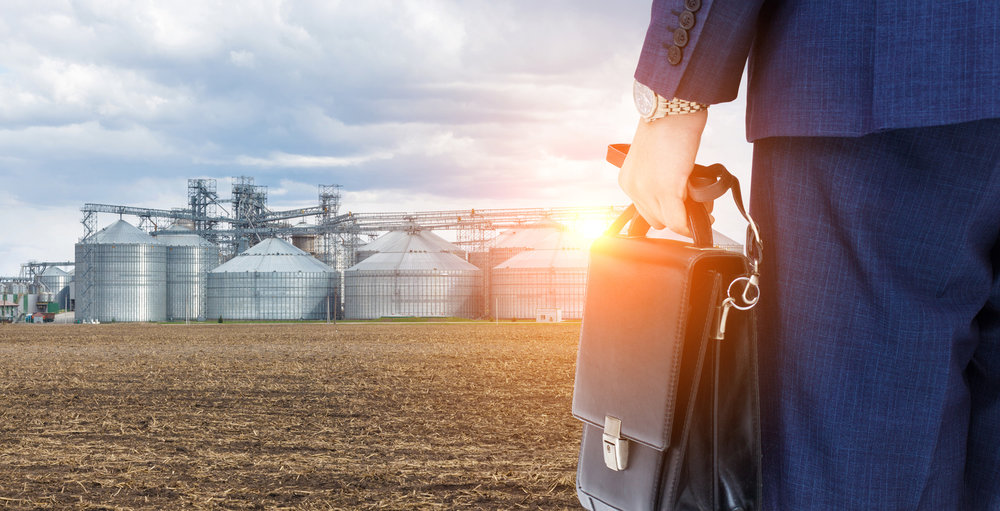 business man with brief case standing in field with silos in the background