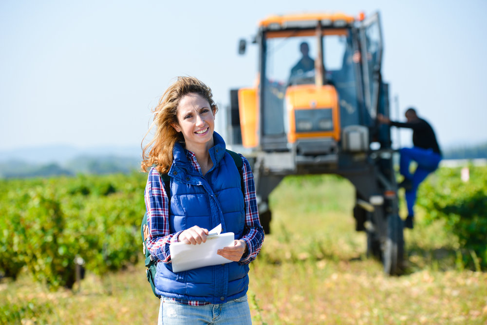 woman farmer in field with tractor in the background